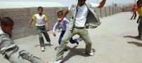 بهرام رادان در حال بازی فوتبال با کودکان افغان