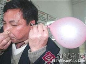 مردی كه با گوش های خود بادكنك باد می كند +عكس
